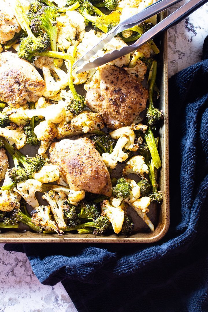 Sheet pan chicken thighs with broccoli and cauliflower.