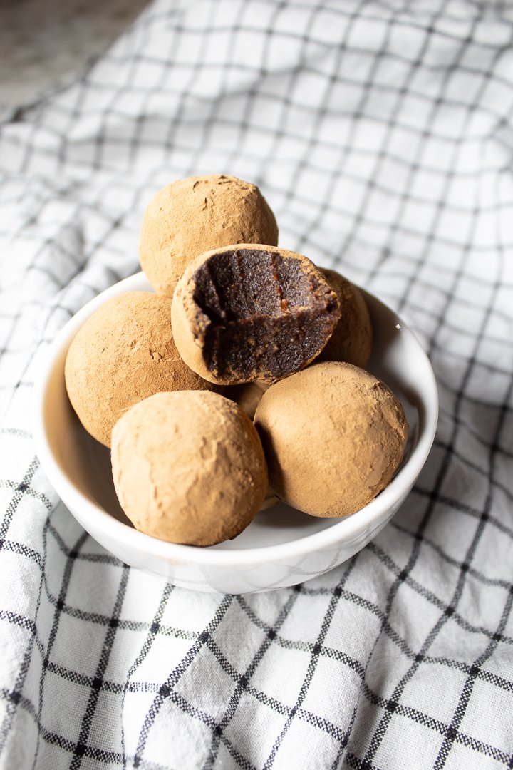 Carob Collagen Bliss Balls in a bowl with a bite taken out.