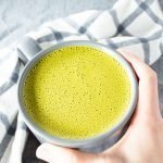 Hand reaching for Easy Coconut Milk Matcha Latte in a mug.