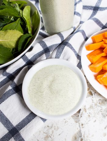 AIP ranch dressing in a bowl with carrots and greens.