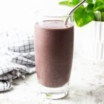 Blueberry Ginger Collagen Smoothie in a glass with a metal straw