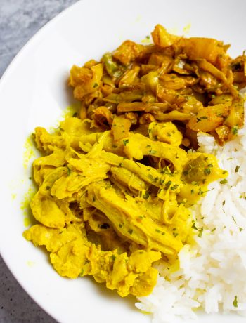 Effortless Instant Pot Turmeric Chicken on a white plate with rice and cabbage..