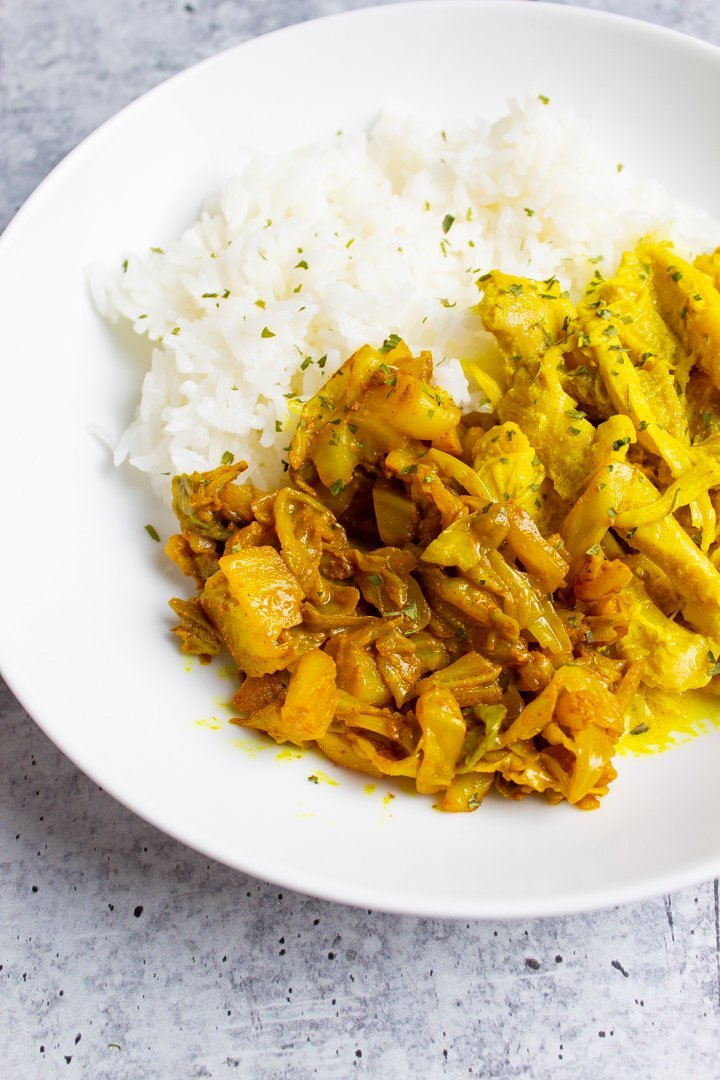 Turmeric Spiced Braised Cabbage on a plate with Turmeric Chicken and rice..