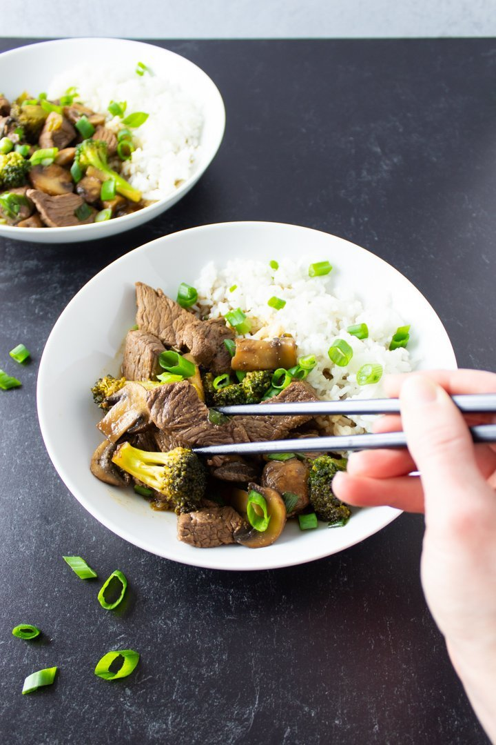 Chopsticks reaching for a piece of beef in an AIP Beef Stir Fry.