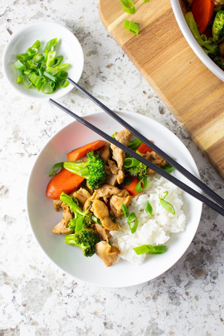 Top view of Easy AIP Chicken Stir Fry served up in a white bowl with chopsticks.