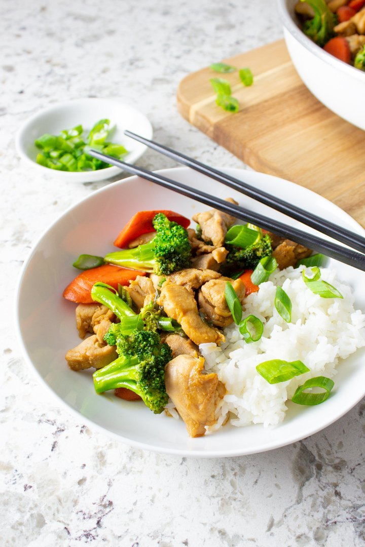 Easy AIP Chicken Stir Fry served up in a white bowl with chopsticks.