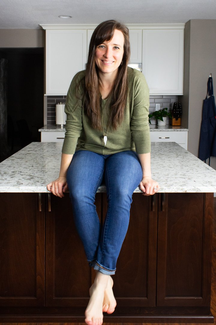 Andrea, the Hurried Health Nut, sitting on the counter in jeans and a sage green sweater.