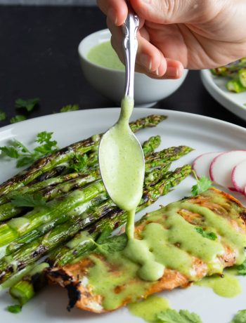 Cilantro Lime Coconut Yogurt Sauce being spooned over grilled shrimp and asparagus on a white plate.