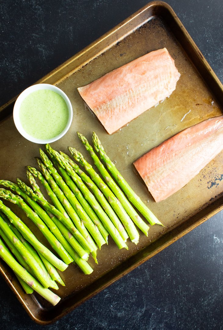 Raw salmon and asparagus with a small bowl of cilantro lime sauce arranged on a sheet pan.
