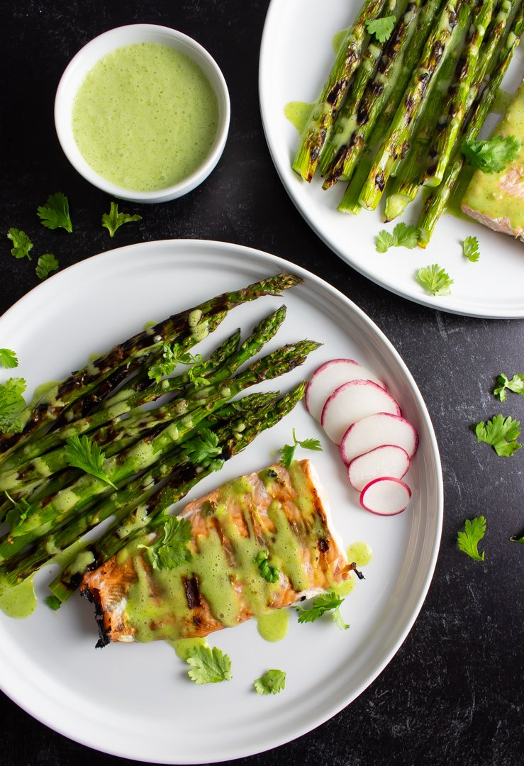 Top view of Grilled Salmon and Asparagus with a small bowl of Cilantro-Lime Sauce on white plates with a textured black background.