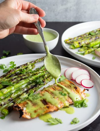 Grilled Salmon and Asparagus with a spoonful of Cilantro-Lime Sauce being drizzled over the top.