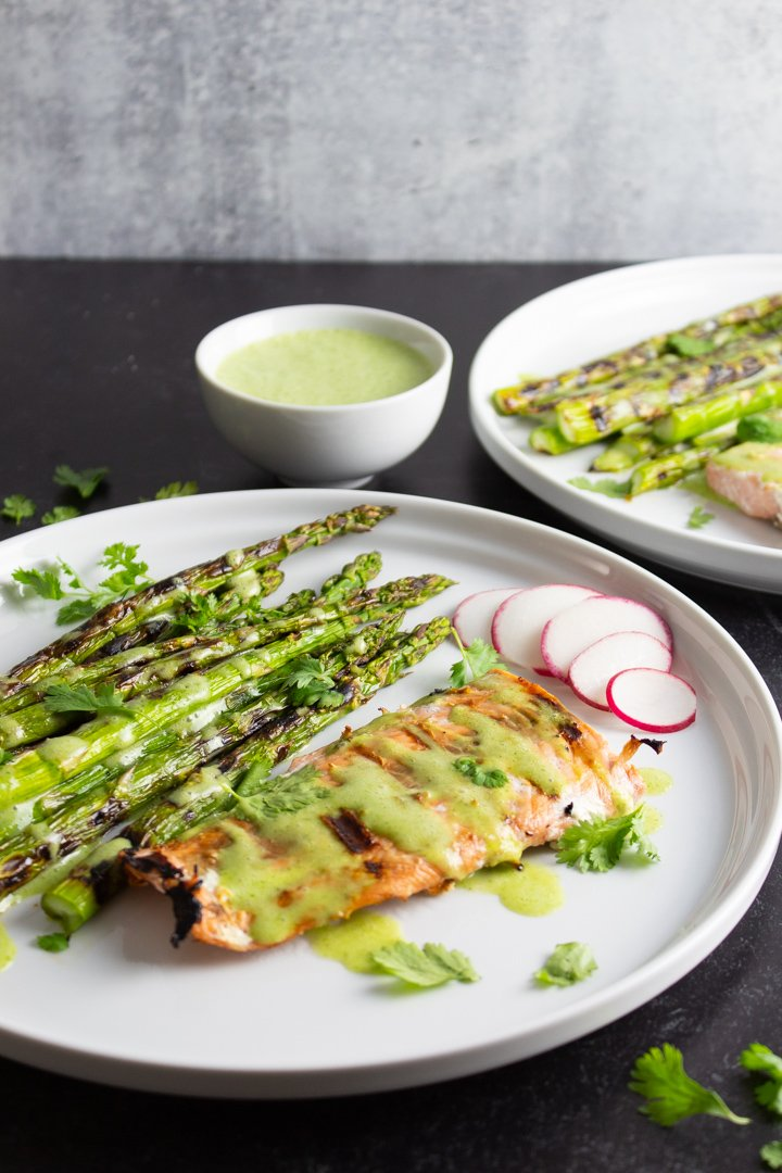 Side view of Grilled Salmon and Asparagus with a small bowl of Cilantro-Lime Sauce on white plates with a textured black background.