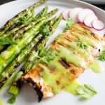 Close up of Grilled Salmon and Asparagus with Cilantro-Lime Sauce drizzled over the top, on a white plate.