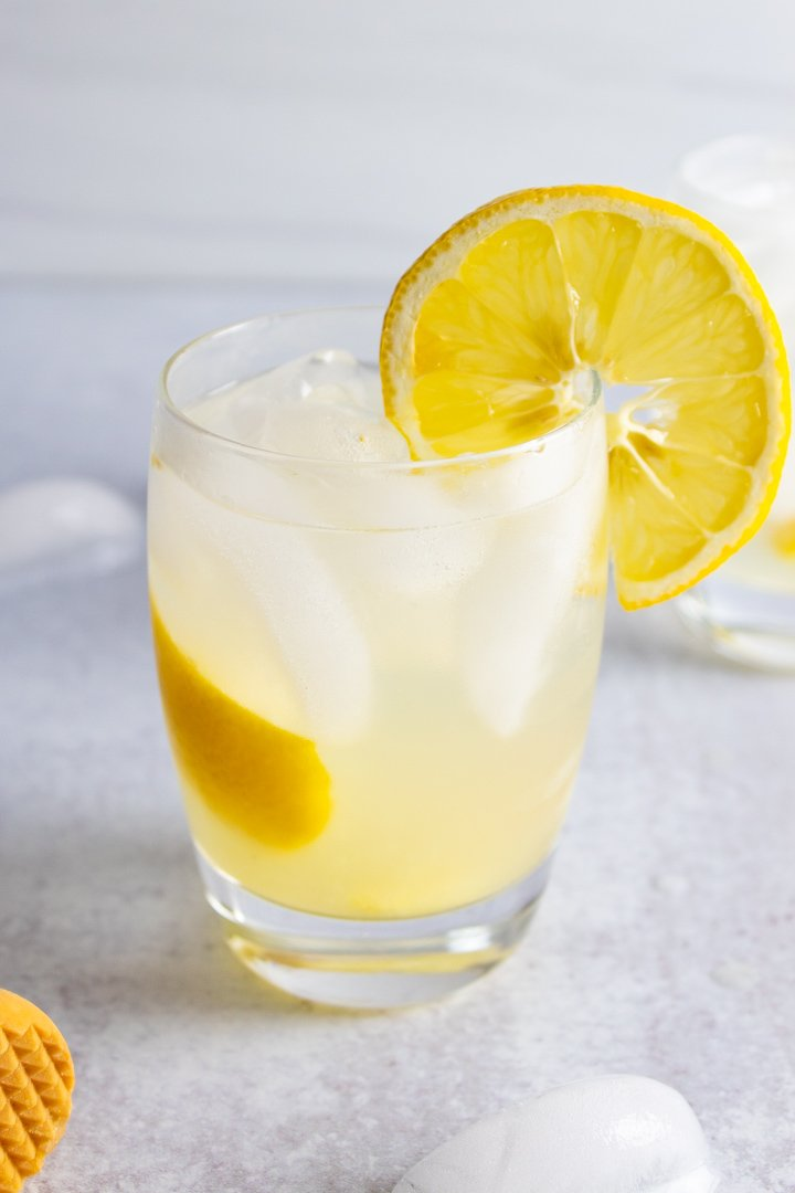 AIP Lemon Ginger Spritzer mocktail in a small glass with a lemon.