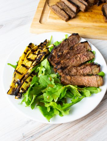 Balsamic grilled steak, summer squash and arugula on a white plate with a wood cutting board.