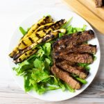 Top view of balsamic grilled steak, summer squash and arugula on a white plate with a wood cutting board.