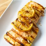 Lemon Turmeric Grilled Salmon on a white plate with two slices of grilled lemon on top.