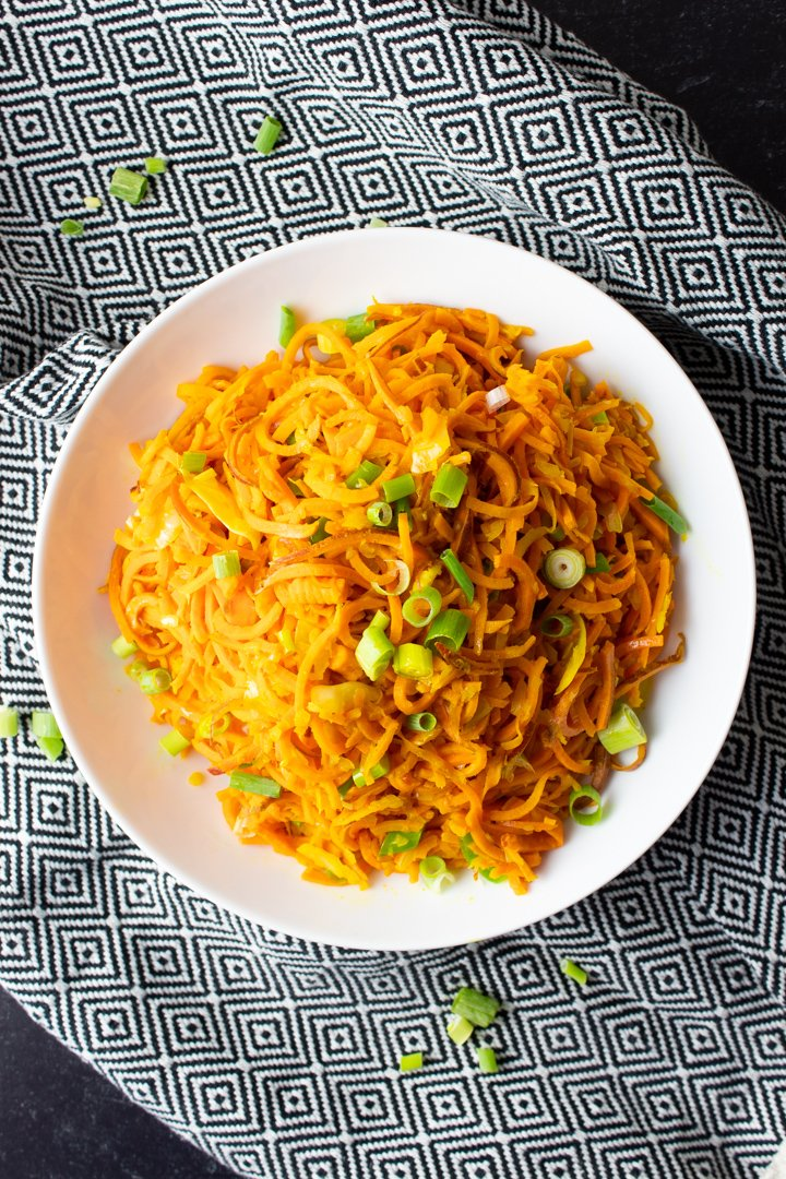 Top view of Sweet Potato Noodle Salad in a white bowl on a black and white kitchen towel.