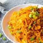 Close up of Sweet Potato Noodle Salad in a white bowl on a black and white kitchen towel.