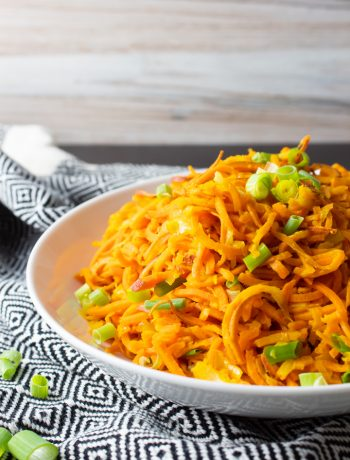 Straight on shot of Sweet Potato Noodle Salad in a white bowl on a black and white kitchen towel with a wood textured background.