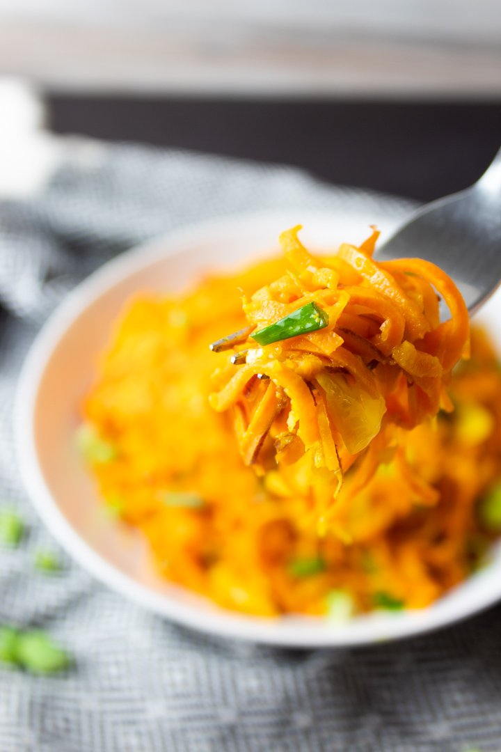 Close up of a forkful of Sweet Potato Noodle Salad with a blurred background.