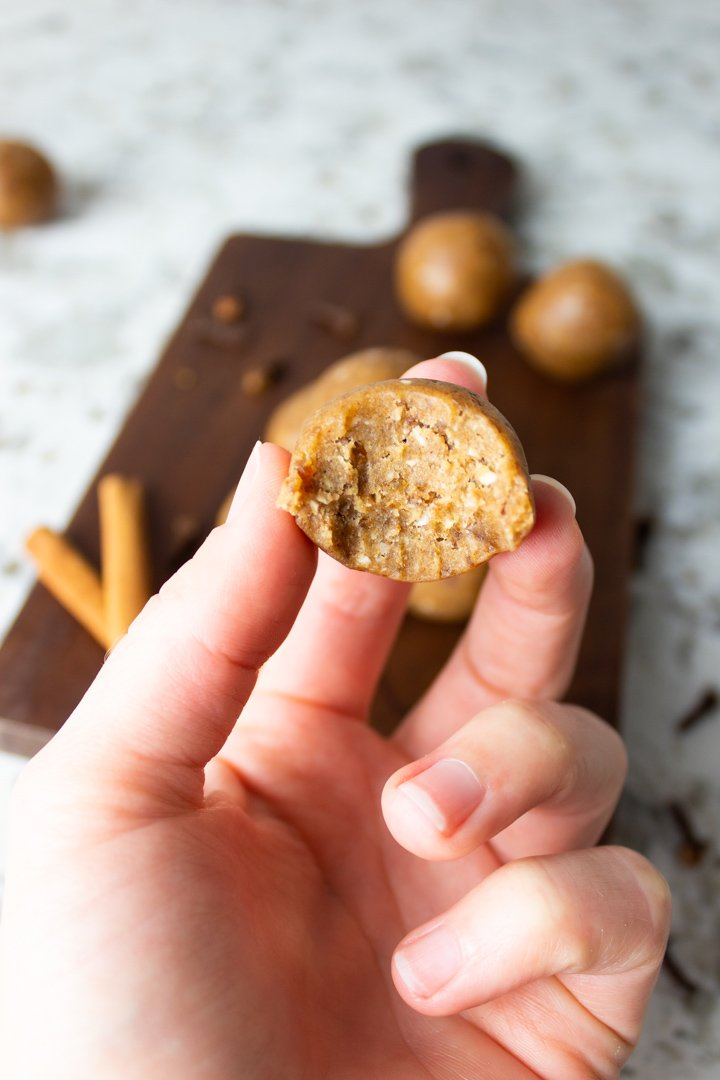 A hand holding a Chai Collagen Bliss Ball with a bite taken out of it.
