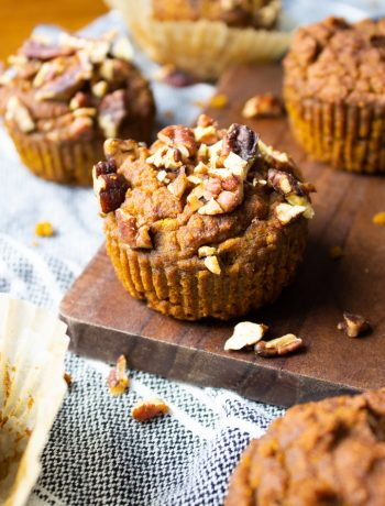 Close up of AIP Pumpkin Muffins on a striped kitchen towel with a wood serving board.