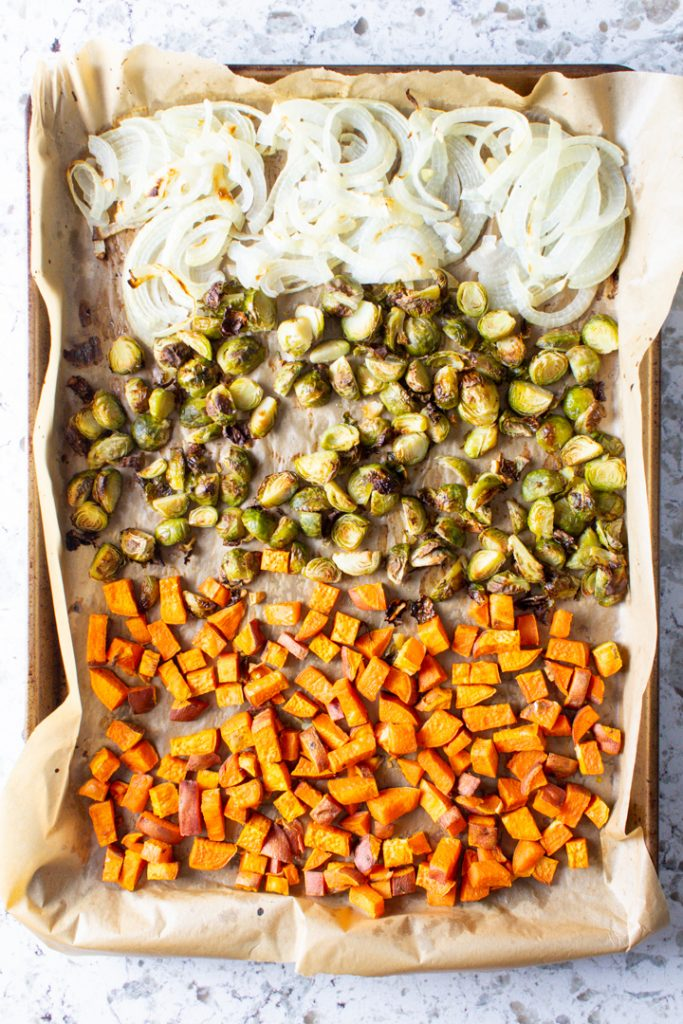 Top view of a sheet pan full of roasted sweet potatoes, brussels sprouts, and onions.