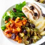 45º angle view of Paleo Autumn Harvest Bowls in white bowls with a plaid kitchen towel.